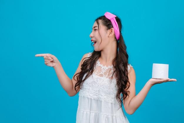 Fille portant un pyjama blanc tenant un papier de soie dans la main sur le bleu.