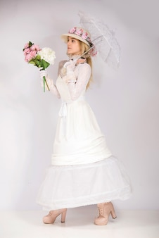Fille portant un style de mode du 19ème siècle, lady corset renaissance de la haute société et jupe longue tenant un ventilateur de soleil heureux et souriant