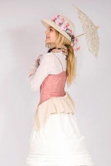 Fille portant un style de mode du xixe siècle, lady corset renaissance de la haute société et jupe longue tenant un pare-soleil heureux et souriant