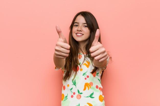 Fille portant un vêtement d'été contre un mur rouge avec le pouce levé, applaudit à quelque chose, soutient et respecte le concept.