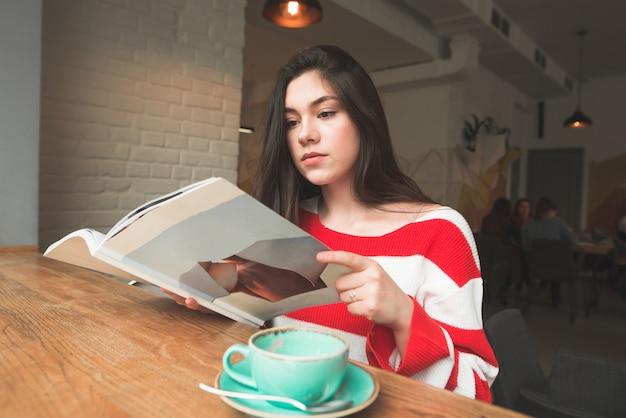 Fille portant des vêtements décontractés, assise dans un café à la table et se concentrant en lisant un magazine