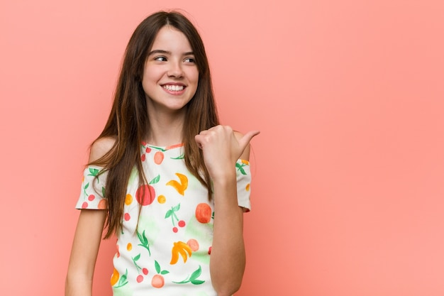 Fille portant des vêtements d'été contre un mur rouge pointe avec le pouce, riant et insouciant.
