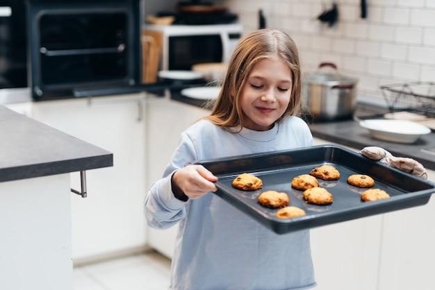 La fille porte un plateau avec des biscuits qu'elle a fait elle-même.