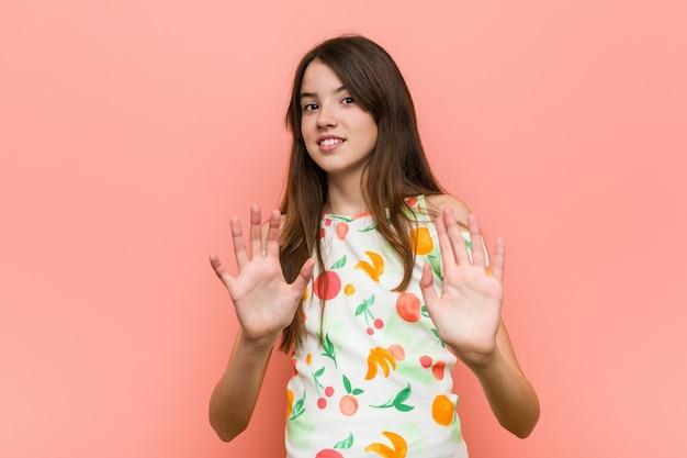 Une fille porte des vêtements d'été contre un mur rouge et rejette quelqu'un qui montre un geste de dégoût.