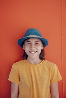 Fille, porter, chapeau bleu, debout, contre, mur rouge