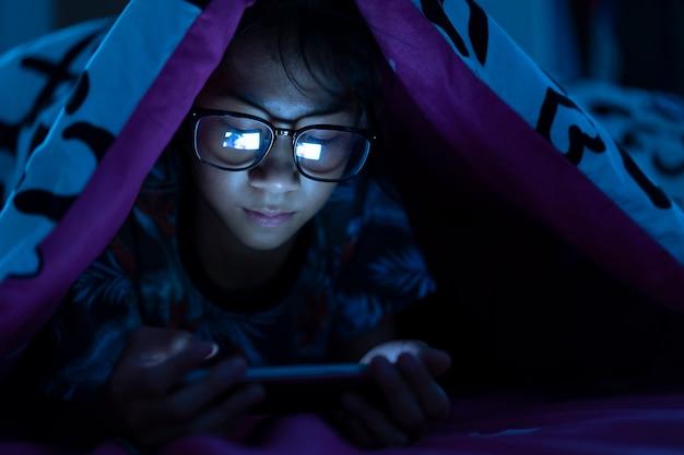 Fille porter des lunettes à l'aide d'un téléphone portable sur un lit sombre dans la chambre