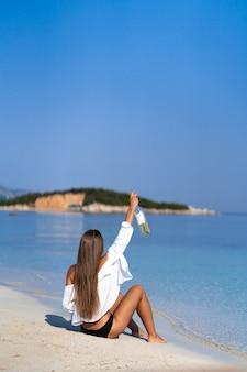 Fille posant avec de l'alcool. athlétique femme heureuse jogging en maillot de bain noir sexy à la mode en profitant du soleil. mode de vie sain. formes parfaites de fitness.