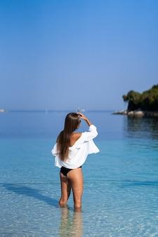 Fille posant avec de l'alcool. athlétique femme heureuse jogging en maillot de bain noir sexy à la mode en profitant du soleil. mode de vie sain. promenade amusante. formes parfaites de fitness.