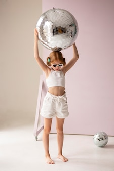 Fille posant avec boule disco full shot