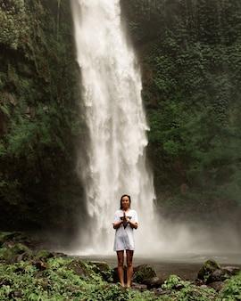 Fille posant dans le contexte d'une cascade