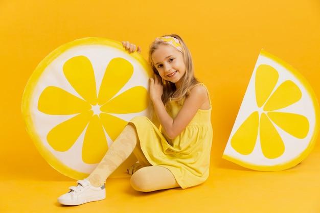 Fille posant avec des décorations de tranches de citron