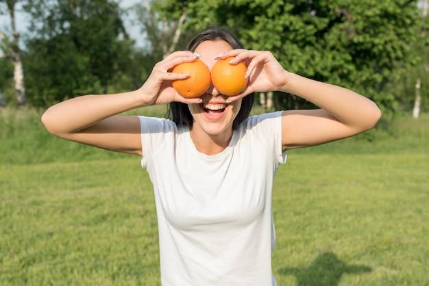 Fille posant avec deux oranges