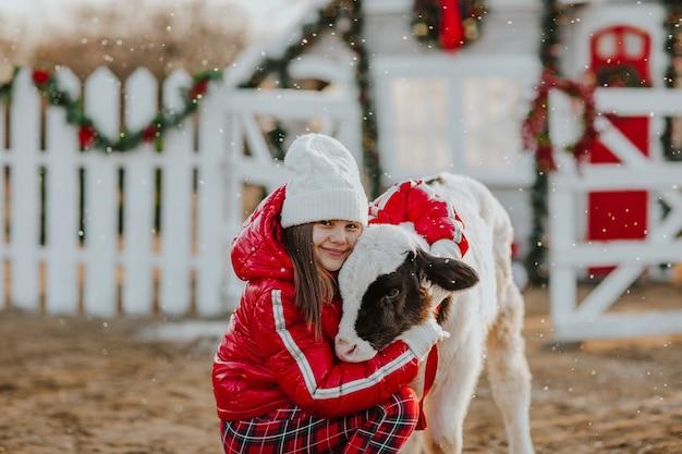 Fille posant avec jeune taureau à la ferme de noël blanche. il neige.