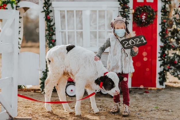 Fille posant avec jeune veau à la ferme de noël blanche