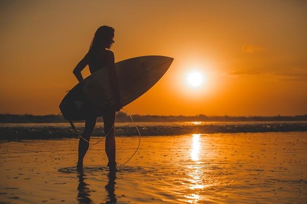Fille posant avec une planche au coucher du soleil