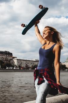 Fille posant avec planche de skate