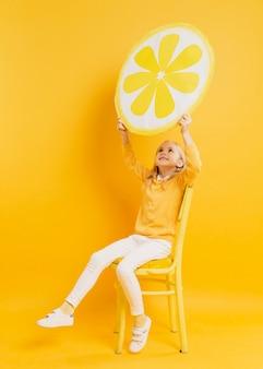 Fille posant tout en tenant la décoration de tranche de citron