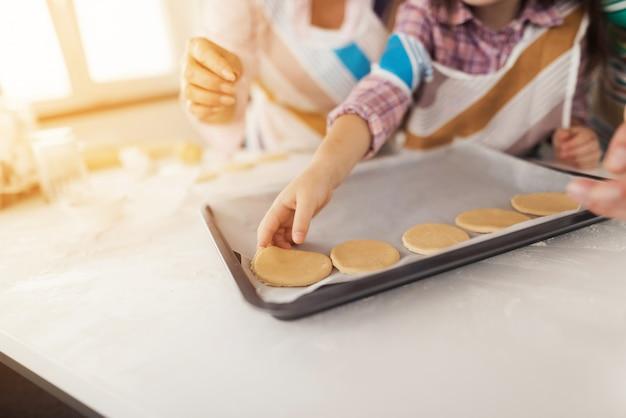 Fille pose des biscuits sur une plaque à pâtisserie