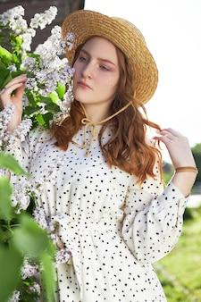 Fille pose dans un buisson de lilas au printemps. portrait romantique d'un enfant en fleurs à la lumière du soleil