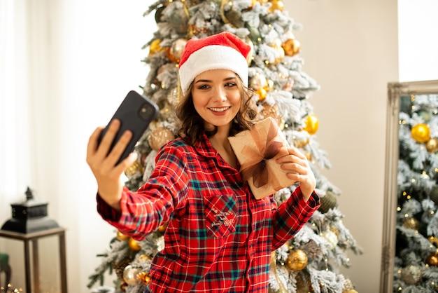 La fille pose et prend un selfie près du sapin de noël. une femme félicite un parent en ligne par téléphone. elle tient un cadeau dans sa main et sourit.