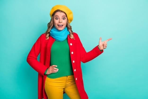 Une fille positive étonnée pointe l'index copyspace impressionné incroyable promotion d'annonces crier wow omg indiquer porter des pantalons de couvre-chefs pantalons isolés sur fond de couleur sarcelle
