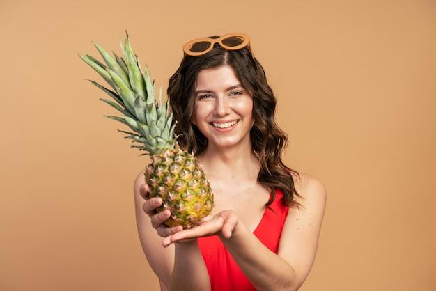 Fille positive et souriante tenant un ananas dans ses mains, elle le représente