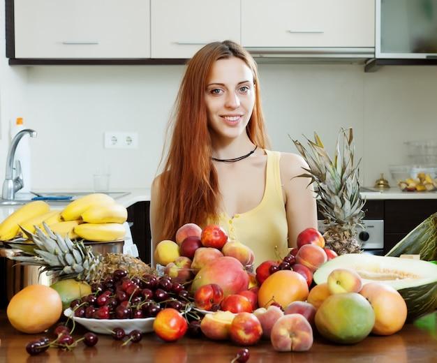 Fille positive avec tas de fruits