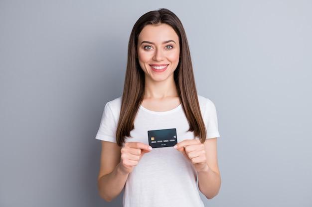 Une fille positive tient une carte de crédit et recommande un service bancaire