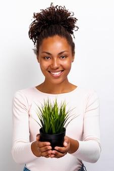 Fille avec un pot d'herbe dans ses mains qu'elle tient dans un bras droit