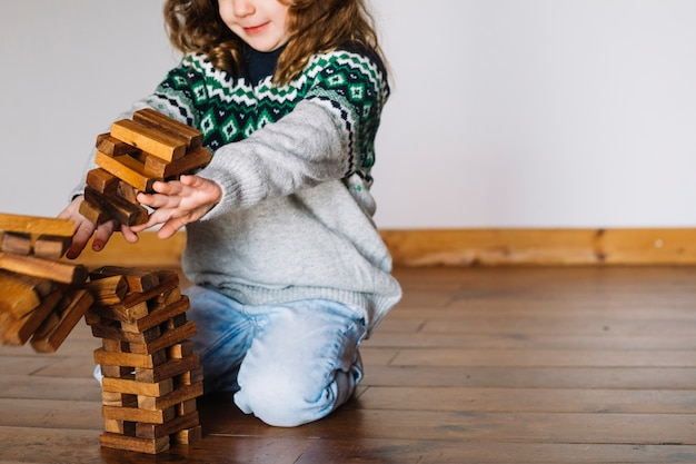 Fille en poussant des blocs de bois empilés