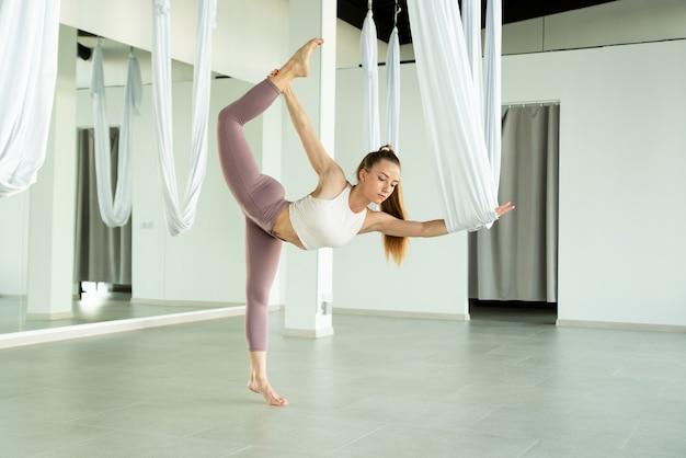 La fille pratiquant le fly yoga dans une pièce vide