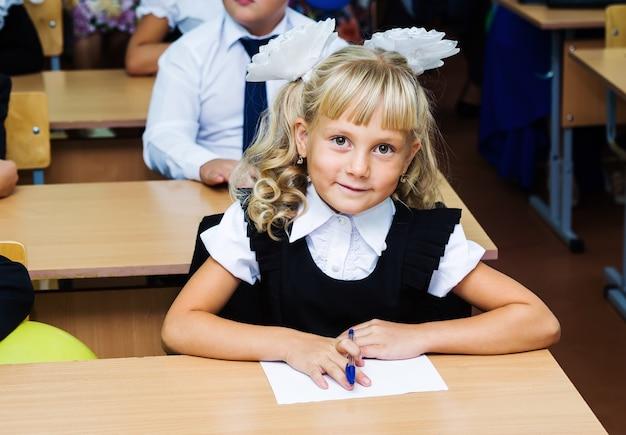 Fille de première année assis à un bureau sur la première leçon