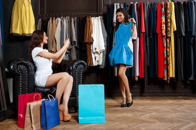 Fille prenant une photo d'un autre essayant de s'habiller au centre commercial.