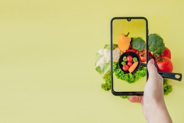 Fille prenant une photo de la nourriture végétarienne sur la table avec son smartphone. concept végétalien et sain.