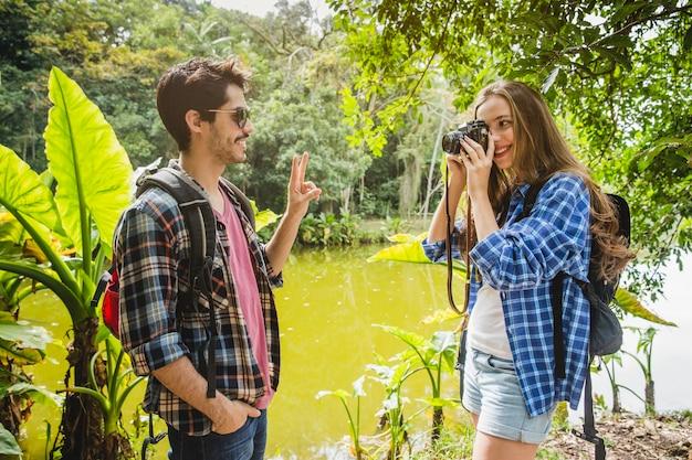 Fille prenant une photo de petit ami dans la jungle
