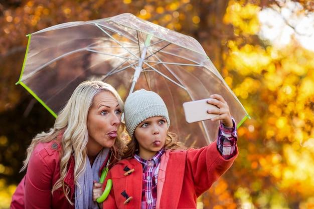Fille prenant selfie avec mère au parc