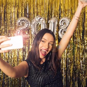 Fille prenant selfie avec smartphone brillant sur la célébration du nouvel an