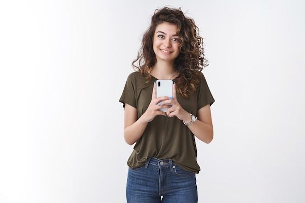 Fille prenant votre photo. sympathique jeune petite amie aux cheveux bouclés tenant un smartphone capture une photographie verticale souriant largement appareil photo, debout sur fond blanc, ami de tir
