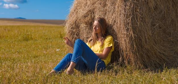Une fille prend un bain de soleil dans le foin. vie du village : récolte du foin pour l'hiver. l'alimentation animale.