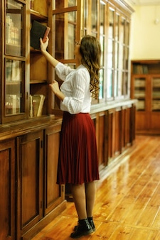 La fille prend des livres de la bibliothèque