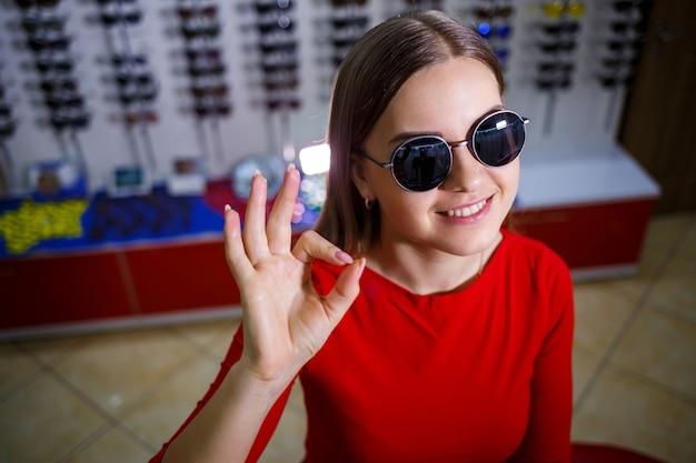 La fille prend des lunettes de soleil. boutique de lunettes. correction de la vue. porte-lunettes