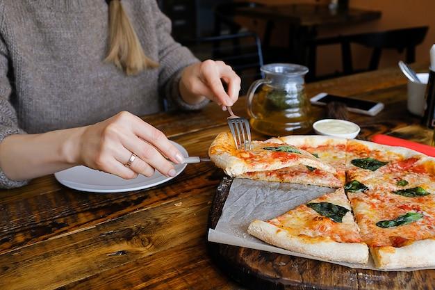 La fille prend un morceau de pizza végétarienne avec du fromage mozzarella, des tomates, des épices et du basilic frais. délicieuse cuisine italienne. pizza margarita en tranches sur une planche de bois. fermer. délicieux déjeuner, collation