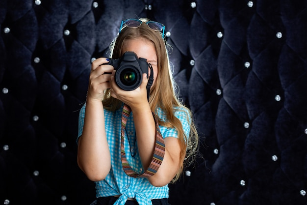 Une fille prend des photos avec un appareil photo reflex dans le studio