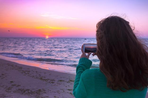 La fille prend des photos sur le lever de soleil de smartphone à la mer