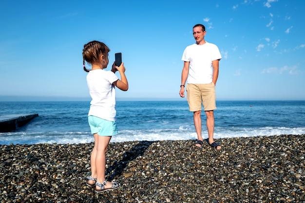 Une fille prend des photos de papa et filme une vidéo au téléphone alors qu'il se repose en mer