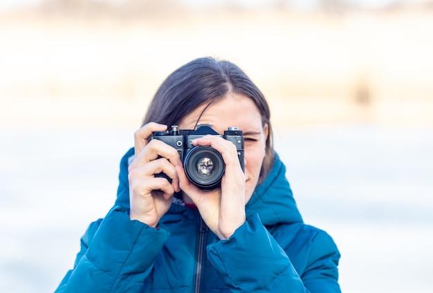 La fille prend des photos avec un vieil appareil photo.