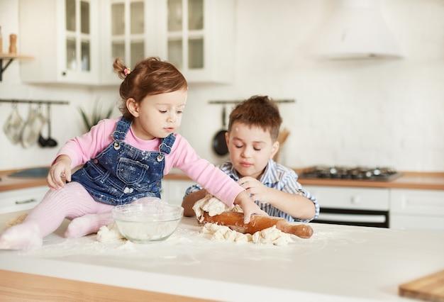 La fille prend le rouleau à pâtisserie, le garçon pétrit la pâte