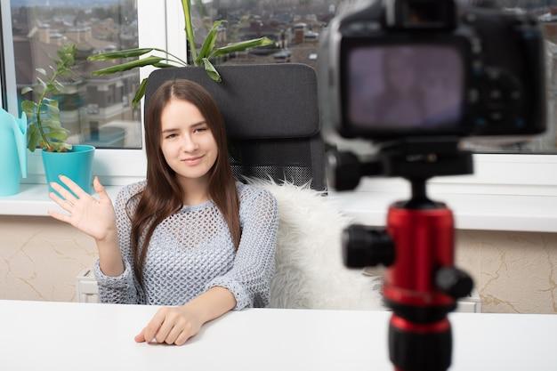 Une fille prend une vidéo d'elle-même à la maison devant une caméra