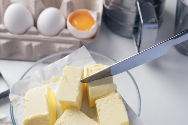Fille préparant des biscuits dans la cuisine, coupant du beurre, gros plan. une femme prépare de la pâte pour de délicieuses pâtisseries. instructions pas à pas. mélanger différents ingrédients pour la pâte. arrière-plan.