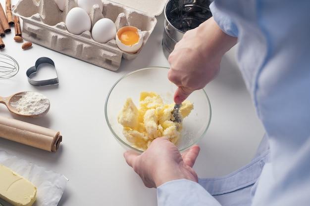 Fille préparant des biscuits dans la cuisine, mélangeant tous les ingrédients dans une tasse, gros plan. une femme prépare de la pâte pour de délicieuses pâtisseries. instructions pas à pas. arrière-plan.